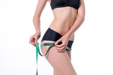 Fit and healthy young lady measuring her hips with a tape measure in centimeters and millimeters. She has her black gym exercise outfit on. Isolated image on white. - 173469456