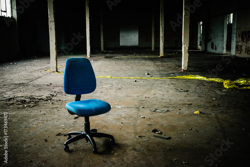 Aluminium Gebouw in Puin Office chair sits in the middle of an empty, abandoned warehouse.