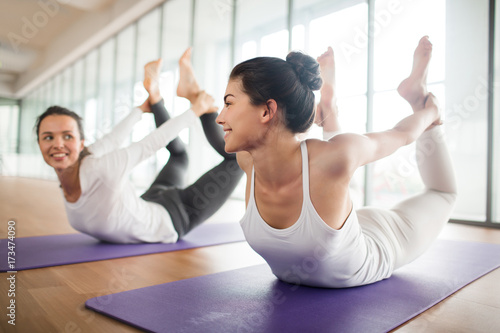 Sticker Active and flexible girls lying on bellies and holding legs in hands while practicing yoga on mats