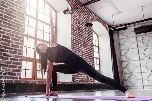 Fototapeta Young sporty woman practicing yoga doing triangle pose, trikonasana, on mat