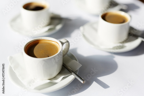 Papiers peints Cafe Three porcelain cups of black aromatic fresh hot coffee on white paper napkins and saucers