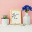 "Card with inspiration quote ""do small things with great love"" in a wooden photo frame in front of pale pink pastel background"