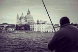 Man catching fish in Punta della Dogana and Basilica di Santa Maria della Salute black and white background, Venice background view, Venice in Italy, Symbol of Venice, bw photography theme Venice