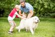 Vater und Sohn spielen mit Hund