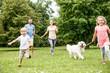 Kinder laufen mit Retriever Hund