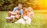 Familie und Kinder mit Hund im Garten - 173535257