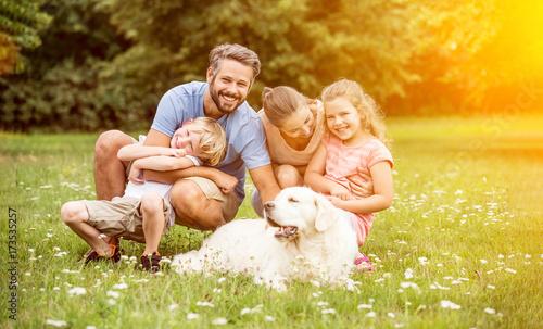 Fototapeta Familie und Kinder mit Hund im Garten