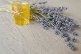 Small glass jar with honey and twigs of lavender flowers - 173538205