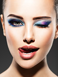 Beautiful face of an young woman with blue makeup of eyes - 173548223