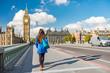 London city urban lifestyle tourist woman walking. Businesswoman commuting going to work on Westminster bridge street early morning. Europe travel destination, England, Great Britain, UK.