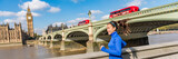 London city lifestyle sport woman running near Big Ben. Asian girl runner jogging training at Westminster bridge with red double decker bus. Fitness athlete happy in London, England, United Kingdom.