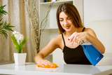 happy woman cleaning table at home - 173559665