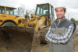 man posing next to the backhoe - 173578099