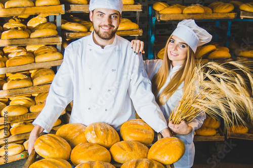 Bakery. Bread. Two bakers. Young beautiful workers of a bakery on a background of racks with bread. Industrial production of bakery products. Couple. Workers. Boy and girl