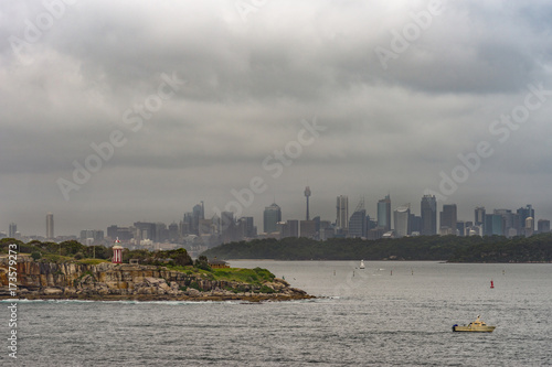 Sydney, Australia - March 21, 2017: South Head cliffs and park with short Hornby lighthouse up front, backed by Sydney skyline under foggy covered cloudscape. Small boat and buoys.
