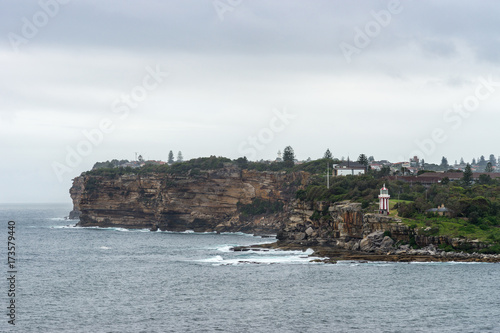 Staande foto Sydney Sydney, Australia - March 21, 2017: South Head cliffs and park with short Hornby lighthouse, backed by green vegetation under foggy light cloudscape. Sea water crashing on beach.