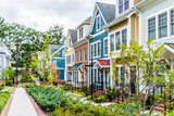Row of colorful, red, yellow, blue, white, green painted residential townhouses, homes, houses with brick patio gardens in summer - 173619428