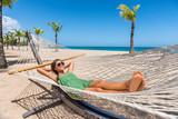 Happy girl relaxing on beach hammock in tropical vacation resort hotel. Holidays in the Caribbean tanning under the sun. Woman wearing sunglasses and green dress relax lying down on sun lounger bed. - 173638272