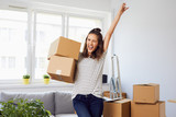 Joyful young woman standing in new apartment with arm raised after moving in - 173654236
