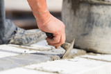 Construction worker working hard and leveling concrete pavement outdoors. - 173658619