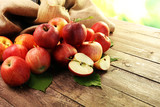 Ripe red apples with leaves on wooden background - 173666488