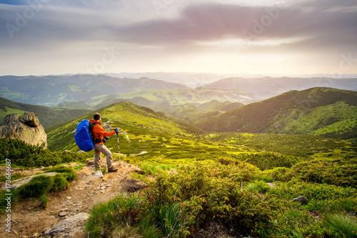 Fridge magnet Traveler Man hiking with backpack admiring a beautiful landscape. HDR foto.
