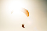 paraglider flying with paramotor on blue sky - 173676242