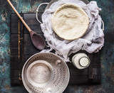 Homemade cheese making with cheesecloth , bottle of milk and wooden spoon on rustic background, top view - 173682685