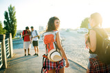 Rear view of two gorgeous girls walking on the street with backpacks and hat. - 173684478