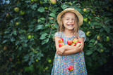Happy little girl holding apples in the garden - 173688403