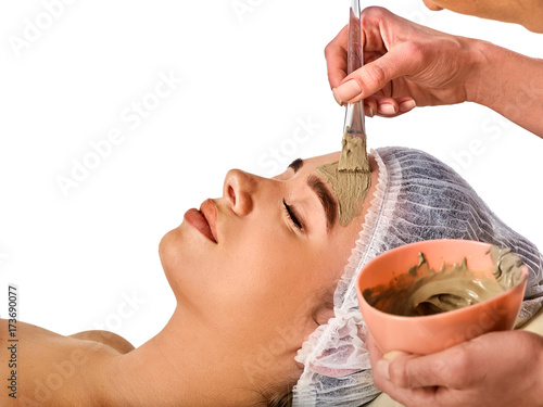 Fotobehang Spa Mud facial mask of woman in spa salon. Massage with clay full face. Girl on with therapy room. Beautician with brush therapeutic procedure isolated background. Masks for skin tightening.