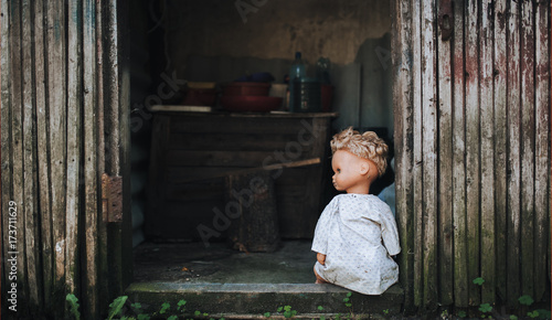 The old doll is left in the doorway of an old abandoned building. Concept of fear and loneliness.