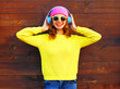 Fashion smiling woman listens to music in headphones, colorful pink hat yellow knitted sweater
