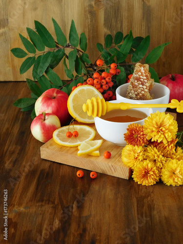 Liquid honey, lemon and rowan berries surrounded by flowers on a wooden board Poster