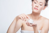 Young, attractive woman using a face cream. - 173747459