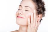 Beautiful young woman smiling and applying eye cream. - 173748494