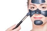 Black charcoal mask application on beautiful woman. - 173748609
