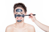 Young woman having a black charcol mask applied on her skin. - 173748862