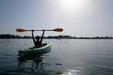 Boy in life jacket on green kayak - 173774056