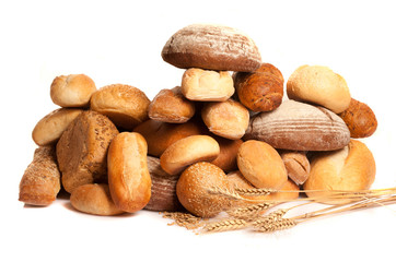 assortment of baked bread with wheat on white background