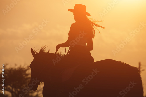 Sunset silhouette of young cowgirl riding her horse Poster