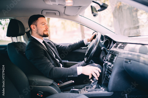 Handsome businessman in the drivers seat in his car and change speed