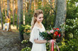 Young blonde bride with a rustic bouquet is posing outdoor in the park. Artwork. Autumn wedding ceremony outdoors.