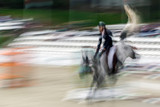 Abstract image with a moving rider and horse at show jumping - 173815824