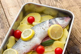 Fish with lemon potatoes and tomatoes ready for the oven - 173824457