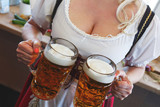 Girl in a traditional dress with a big breasts and deep neckline holds full mugs of beer. - 173824685