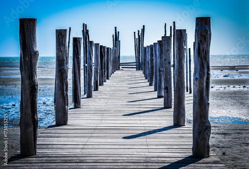 Plexiglas Pier rustic wooden jetty in a low tide