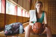 Portrait of female basketball player sitting on bench
