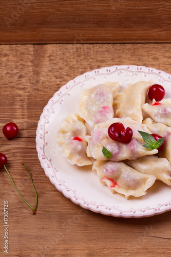 Dumplings, filled with cherries. Varenyky, vareniki, pierogi, pyrohy - popular dish in East Europe. Vertical - 173877215