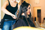 Professional hairdresser dyeing hair of her client - 173879447